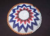An old Zulu beaded Mbenge or beer pot lid.
